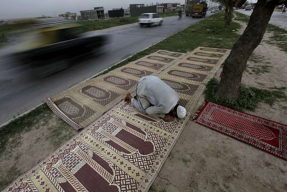 Vehicles move past a Pakistani worker offering the daily Asr prayer, the afternoon prayer, in a street on the outskirts of Islamabad, Pakistan, Monday, March 18, 2013. (AP Photo/Muhammed Muheisen) Photo: Muhammed Muheisen, Associated Press