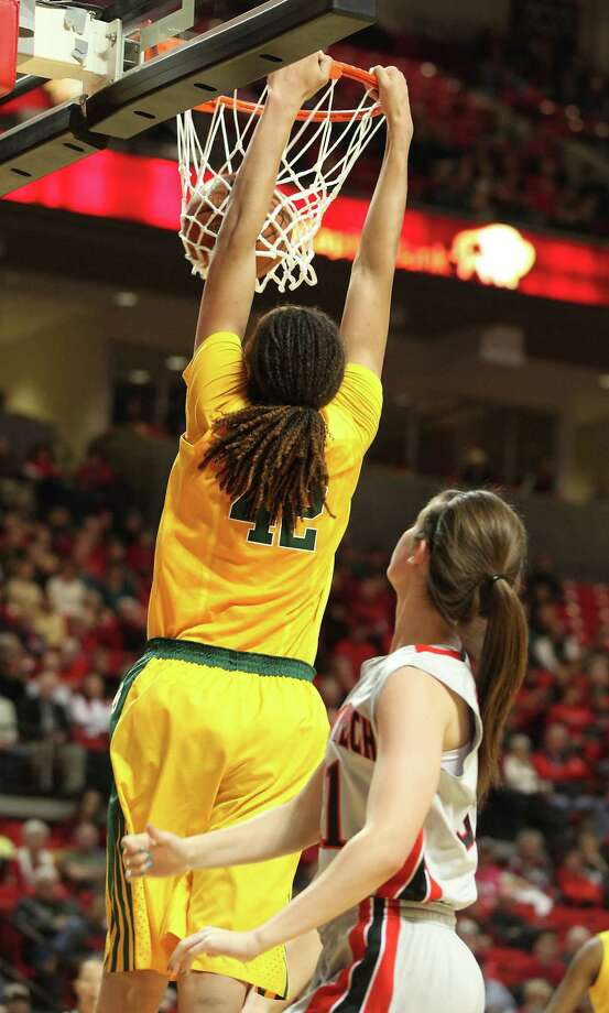 Baylor's Brittney Griner dunks past Texas Tech's Haley Schneider during an NCAA college basketball game in Lubbock, Texas, Wednesday, Jan. 30, 2013. (AP Photo/Zach Long) Photo: Zach Long, Associated Press / FR138474 AP
