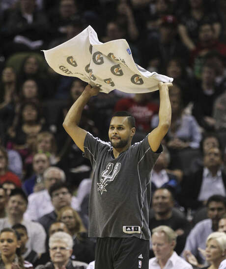 Waving a towel helps Spurs guard Patty Mills stay involved in the game when he's not on the court. Photo: Kin Man Hui / San Antonio Express-News