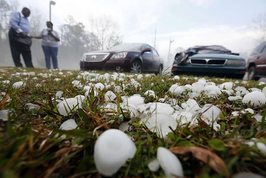 Golfball sized hail litter the ground by  Andrew Stamps and his wife Valorie as they prepare to cover their shattered rear window of her 2009 Toyota Avalon in Pearl, Miss., Monday, March 18, 2013, following a hailstorm that hit communities throughout central Mississippi. The National Weather Service in Jackson says there were a few super cells in central Mississippi and reports of hail up to baseball size in Clinton, golf ball and tennis ball sized in Pearl and Brandon and quarter sized in downtown Jackson, Miss. The Mississippi Emergency Management Agency says severe weather has caused damage in at least 10 counties as the storms moved through parts of the state. (AP Photo/Rogelio V. Solis) Photo: Rogelio V. Solis, Associated Press