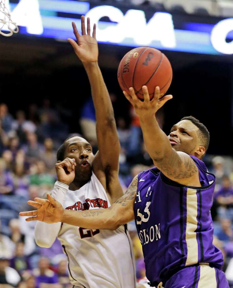 James Madison forward Rayshawn Goins (33) goes to the basket as Northeastern guard Joel Smith (20) tries to defend during the second half of the Colonial Athletic Association Conference tournament championship NCAA college basketball game in Richmond, Va., Monday, March 11, 2013. James Madison won 70-57. (AP Photo/Steve Helber) Photo: Steve Helber