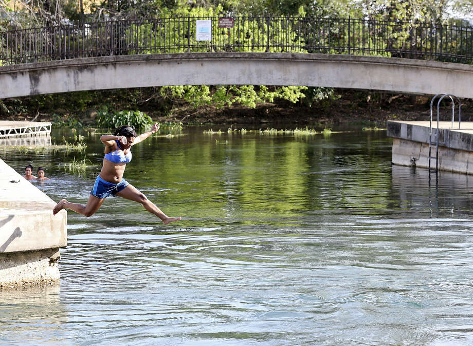 Chellese Brown takes advantage of the heat with a jump in the San Marcos River at Sewell Park in San Marcos. Photo: Edward A. Ornelas / San Antonio Express-News