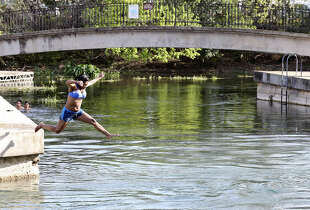 Chellese Brown takes advantage of the heat with a jump in the San Marcos River at Sewell Park in San Marcos.