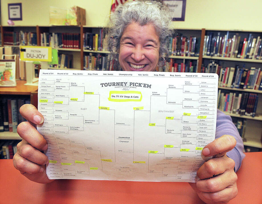 FILE - In this March 31, 2011 file photo, Jefferson High School librarian Diana Inch displays her winning NCAA tournament bracket from Yahoo.com's online contest in Jefferson, Ore. The odds of completing the perfect bracket by picking the higher-seeded team are 35 billion to 1.  (Democrat-Herald, Mark Ylen) Photo: Mark Ylen