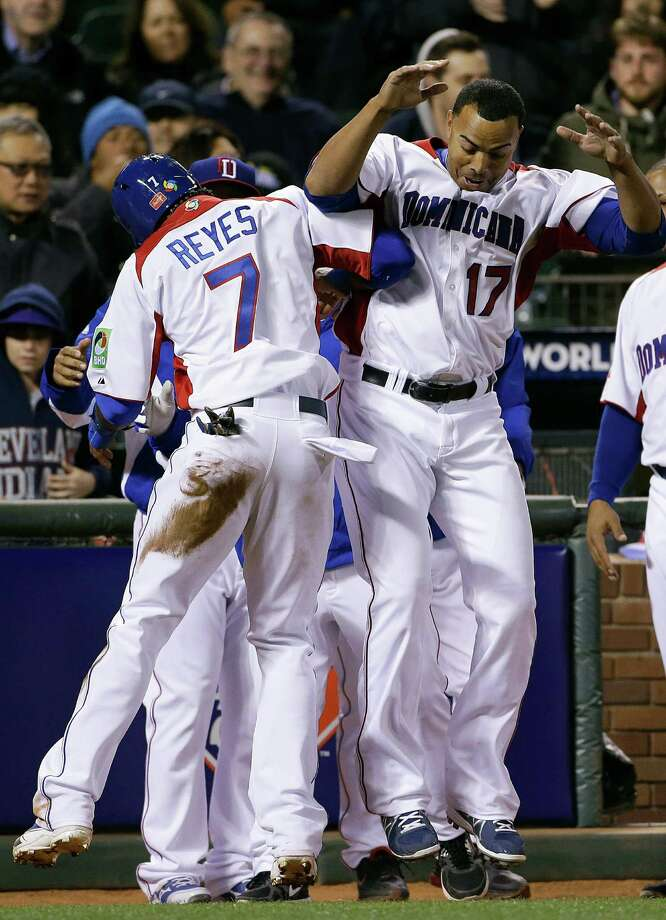The Dominican Republic's Jose Reyes (7) celebrates with Nelson Cruz after scoring in the fifth inning. Photo: Eric Risberg, STF / AP