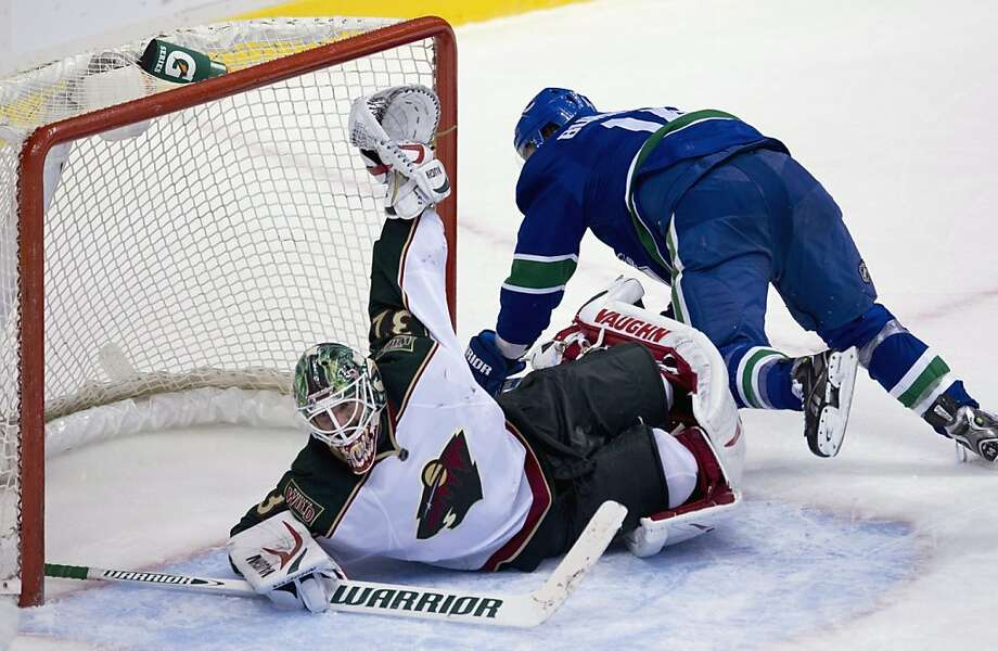 Minnesota goalie Niklas Backstrom keeps the puck out of the net as Alex Burrows trips over him. Photo: Jonathan Hayward, Associated Press