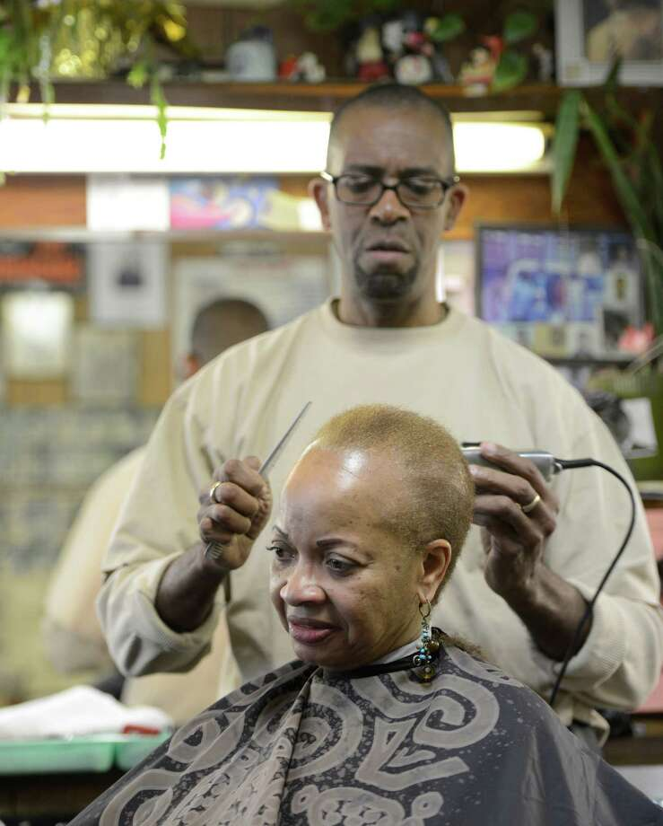 "Barber ""KC"" cuts Vivian Daniels hair at Stancil's Barbershop which was established in 1956 which is still in full swing March 8, 2013, and may be one of the oldest barber shops on Albany, N.Y.  (Skip Dickstein/Times Union) Photo: SKIP DICKSTEIN / 10021482A"
