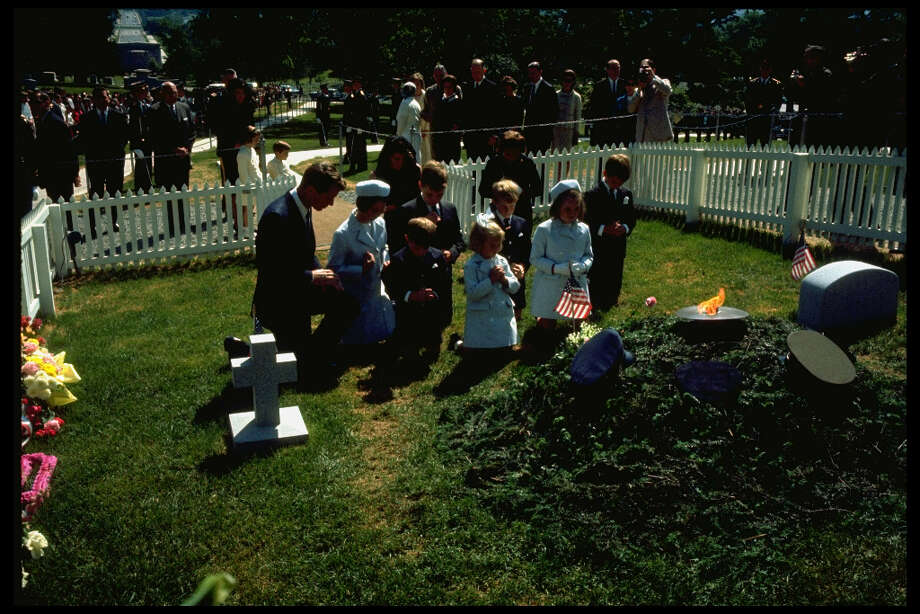 After President John F. Kennedy was assassinated in Dallas on Nov. 22, 1963, most expected him to be buried in the family plot in Holyhood Cemetery, near Brookline, Mass. But Jacqueline Kennedy, the president's widow, declared: He belongs to the people. So he was buried in Arlington National Cemetery. Jacqueline Kennedy had the funeral modeled on Abraham Lincoln's and asked for an eternal flame similar to that of the French Unknown Soldier in Paris. The initial plot was 20 feet by 30 feet and was surrounded by a white picket fence. On Dec. 4, 1963, the two deceased Kennedy children -- Patrick Bouvier Kennedy and an unnamed stillborn daughter -- were reburied in Arlington.This photo shows Robert F. Kennedy, Jacqueline Kennedy and Eunice Kennedy with their children at Kennedy's grave on May 19, 1964, Kennedy's first birthday after his assassination. Photo: Lee Lockwood, Time & Life Pictures/Getty Image / Lee Lockwood