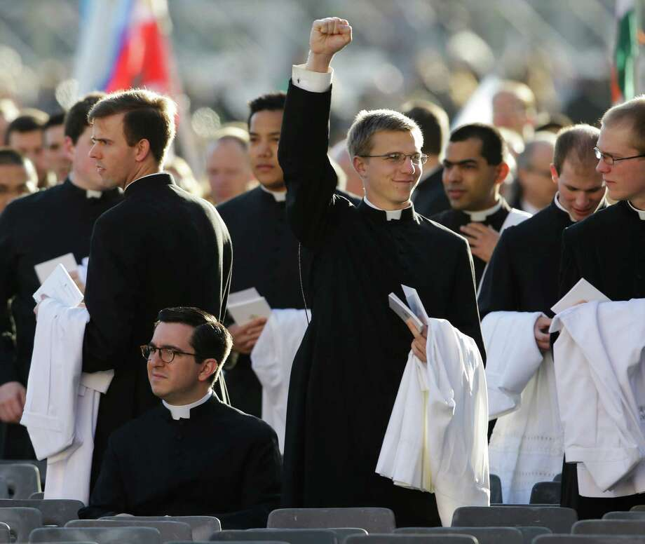 A young priest punches the air as he reaches his seat in Vatican square for the inauguration of Pope Francis in St. Peter's Square at the Vatican, Tuesday, March 19, 2013. Photo: Gregorio Borgia