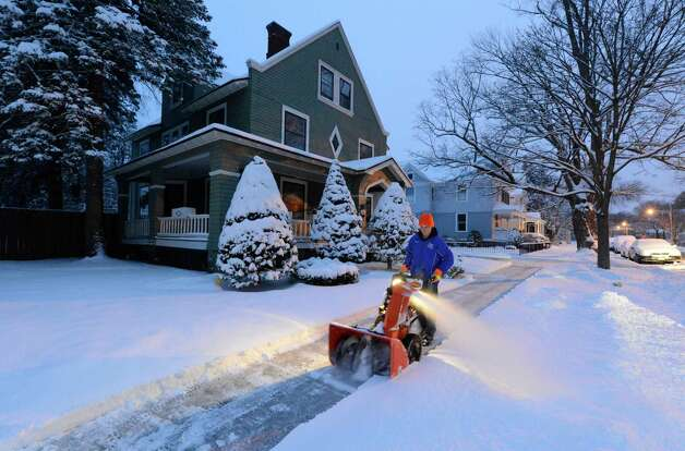 Drew Hasbrouck clears the sidewalk at a residence on 5th Avenue March 19, 2013 in Saratoga Springs, N.Y. after a break in the forecast snow storm that his the area overnight. (Skip Dickstein/Times Union) Photo: SKIP DICKSTEIN