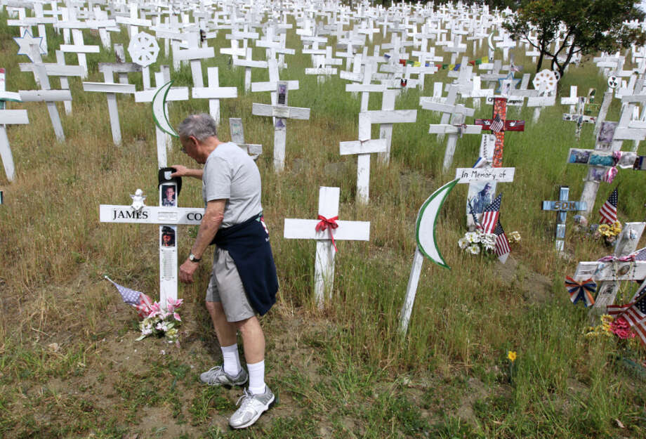Bob Hanson visits the memorial of white crosses on a hillside in Lafayette, Calif. on Friday, March 15, 2013, that he regularly maintains. Anti-war activists erected the monument in late 2006 as a tribute to soldiers who died in the Iraq and Afghanistan wars. Tuesday marks the 10th anniversary of the war in Iraq. Photo: Paul Chinn, The Chronicle / ONLINE_YES