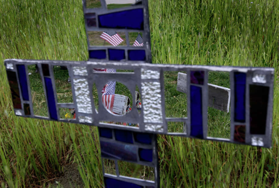 A U.S. flag is reflected in mirrored glass of a personalized memorial cross on a hillside in Lafayette, Calif. Survivors of some soldiers have adopted a cross in memory of their loved one. Photo: Paul Chinn, The Chronicle / ONLINE_YES