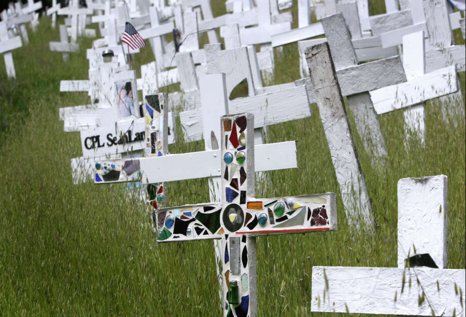 Memorial crosses are arranged on a hillside in Lafayette, Calif. on Friday, March 15, 2013. Survivors of some soldiers have adopted a cross in memory of their loved one. Photo: Paul Chinn, The Chronicle / ONLINE_YES