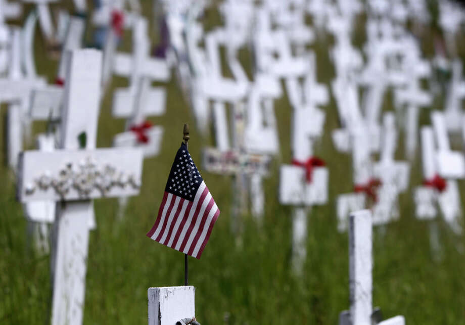 A flag is attached to a memorial cross on a hillside in Lafayette, Calif. on Friday, March 15, 2013. Survivors of some soldiers have adopted a cross in memory of their loved one. Photo: Paul Chinn, The Chronicle / ONLINE_YES