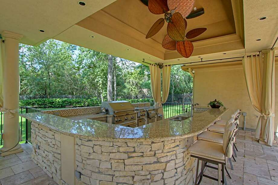 The large outdoor kitchen has custom decorative outdoor ceiling fans and a huge serving bar. Photo: Keller Williams Realty The Woodlands