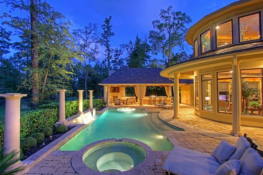 The outdoor living area has a pool, spa, fountains, fire pit and a huge covered outdoor pavilion with a large kitchen and living area with a fireplace and an overhead TV. Photo: Keller Williams Realty The Woodlands
