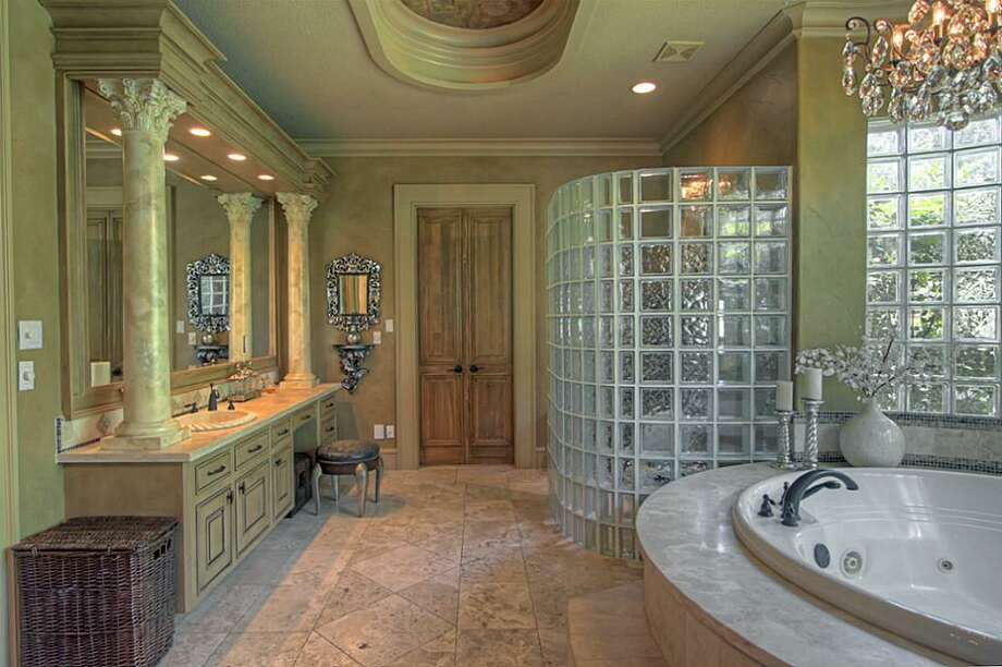 The vanity has seating space and extra drawers/cabinetry. The flooring is 24-inch travertine and the decorative wood columns are painted to match the marble counters. Photo: Keller Williams Realty The Woodlands