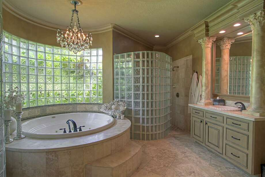 The master bath features an over-sized Jacuzzi soaking tub with marble and travertine surround, a glass block window and shower wall, marble counter tops and a custom crystal chandelier. Photo: Keller Williams Realty The Woodlands