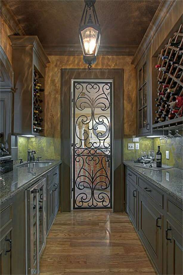A well-equipped wine grotto between the formal dining room and kitchen features custom-wrought iron doors, a built-in wine rack, granite counter tops, a Viking wine fridge and a service window open to the front entry hallway. Photo: Keller Williams Realty The Woodlands