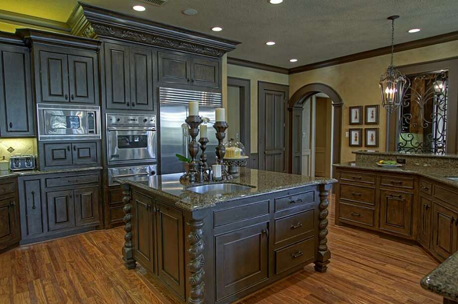 This over-sized island features tons of storage space, additional sink and decorative carved pedestal corners. The SubZero built-in refrigerator has two ice maker drawers. Photo: Keller Williams Realty The Woodlands