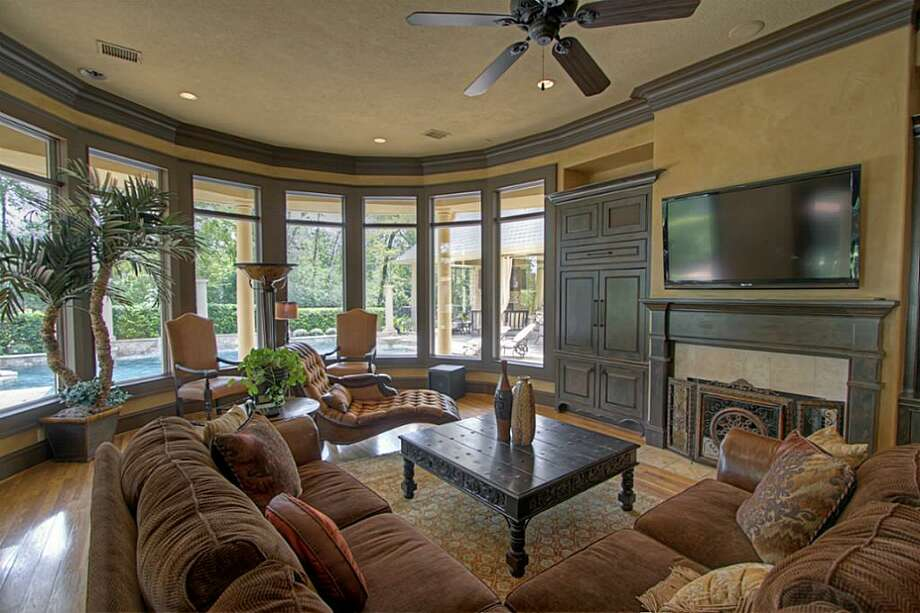 The large den has a wall of picture windows overlooking the pool. Photo: Keller Williams Realty The Woodlands