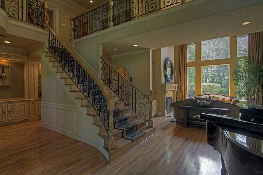 Another view of the formal staircase looking into the formal living room. There is an abundance of storage and built-in display cabinetry behind the staircase. Photo: Keller Williams Realty The Woodlands