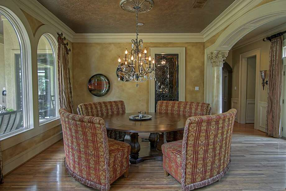 The elegant formal dinning room has faux painted walls and ceiling with decorative wood pillars with carved details. It also adjoins with the wine grotto, which is open to the kitchen. Photo: Keller Williams Realty The Woodlands