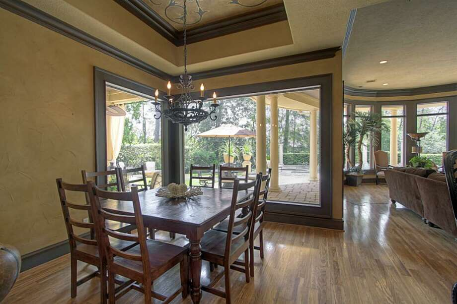 The huge breakfast area has a deep custom-painted tray ceiling, thick double crown molding, large picture windows and a wrought iron chandelier. Photo: Keller Williams Realty The Woodlands