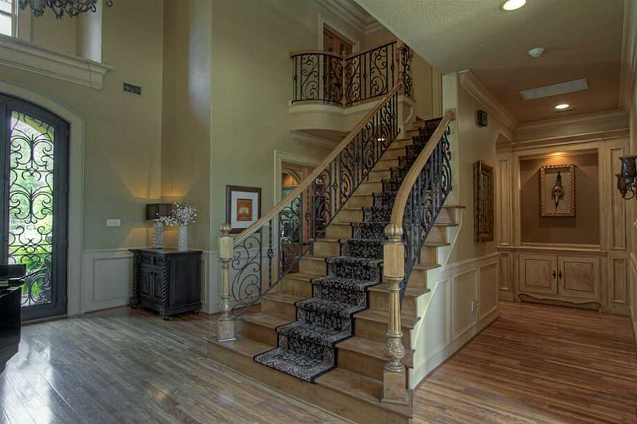 The formal stairway features custom-wrought iron railings and a fabulous carpeted runner. Photo: Keller Williams Realty The Woodlands