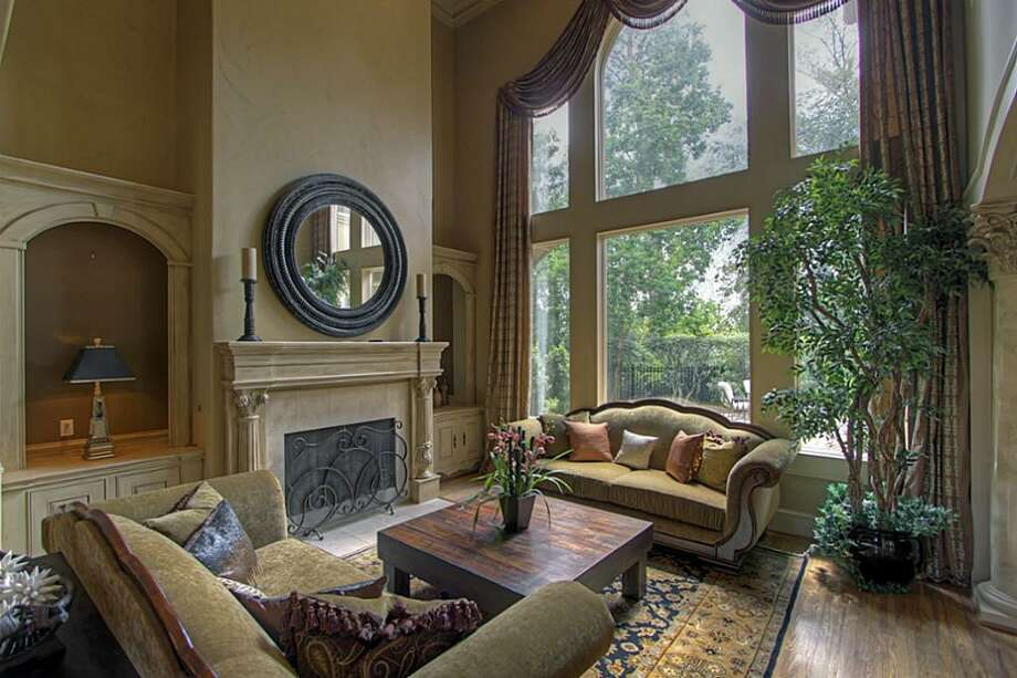 Another feature of this room is the two-story glass windows with custom drapery, overlooking the backyard and gas fire pit. Photo: Keller Williams Realty The Woodlands
