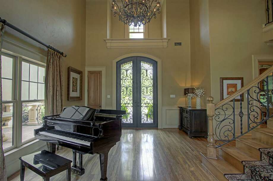 The large elegant foyer features double-wrought iron doors, wood floors and a custom painted rotunda ceiling. Photo: Keller Williams Realty The Woodlands