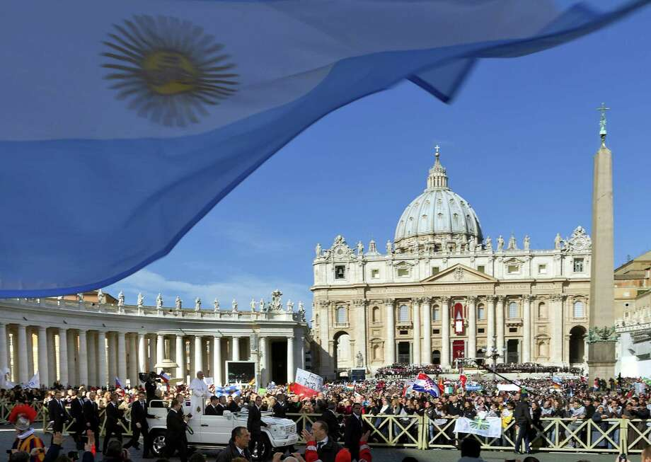 A flag from Argentina waves in the foreground as Pope Francis, bottom, is driven through the crowd prior to his inaugural Mass, in St. Peter's Square at the Vatican, Tuesday, March 19, 2013. Pope Francis thrilled tens of thousands of people on Tuesday gathered for his installation Mass, taking a long round-about through St. Peter's Square and getting out of his jeep to bless a disabled man in a wheelchair in the crowd. Photo: Domenico Stinellis