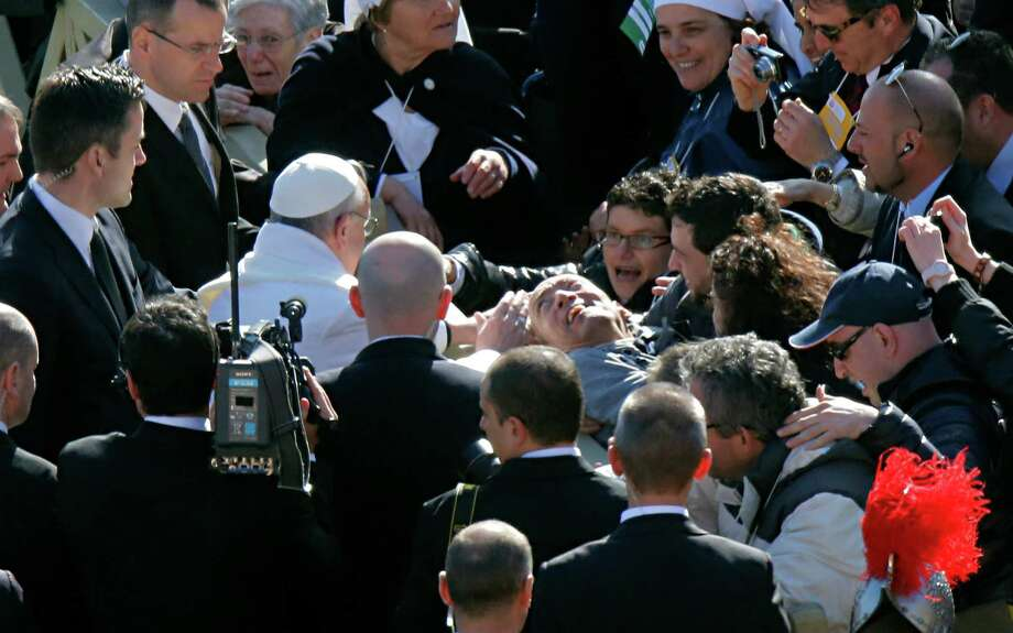 Pope Francis blesses a man prior to his inaugural Mass, in St. Peter's Square at the Vatican, Tuesday, March 19, 2013. Pope Francis thrilled tens of thousands of people on Tuesday gathered for his installation Mass, taking a long round-about through St. Peter's Square and getting out of his jeep to bless a disabled man in a wheelchair in the crowd. Photo: Dmitry Lovetsky