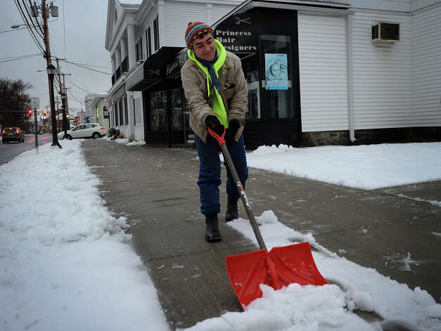 George DaFante shovels snow from the sidewalks outside downtown businesses on Broad Street in Milford, Conn. on Tuesday, March 19, 2013. Photo: Brian A. Pounds / Connecticut Post