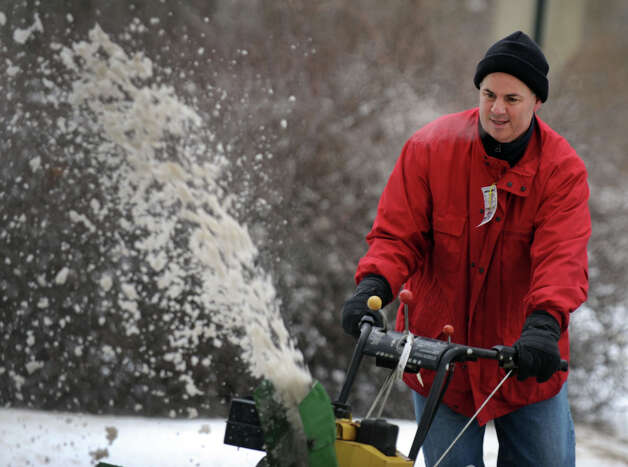 Tom Duffy uses a snowblower to clear snow from his driveway on Judy Drive in Bethel, Conn. Tuesday morning, March 19, 2013, after an overnight snowfall. Photo: Carol Kaliff / The News-Times