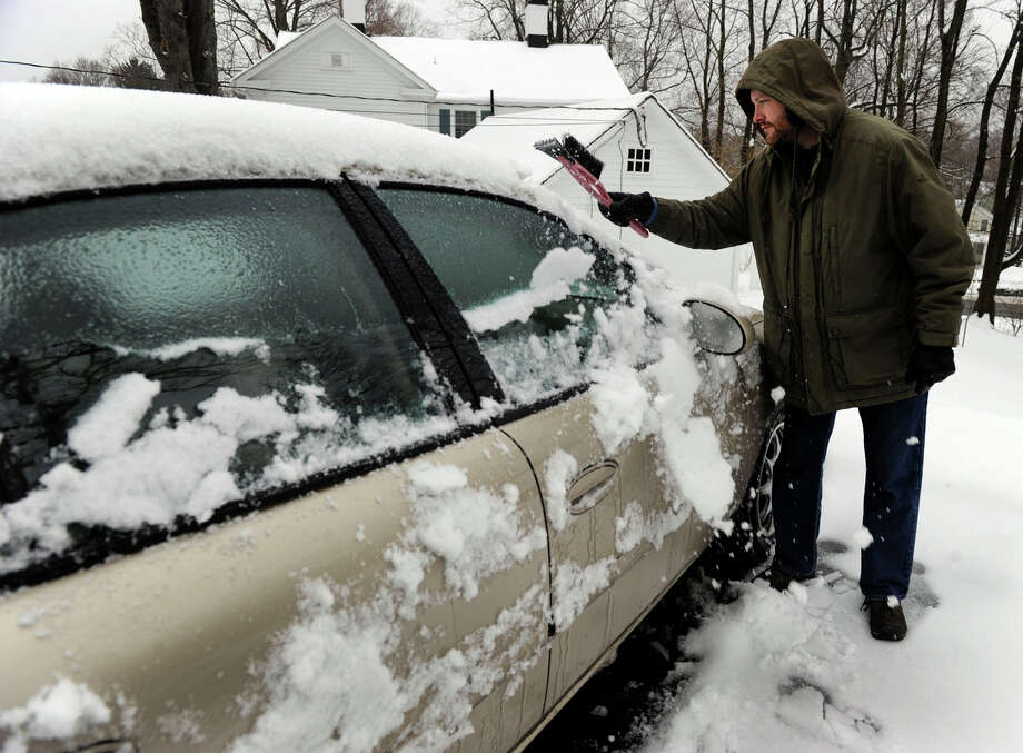 Chris Meyer clears snow from his car on Barnum Hill Road in Bethel, Conn., Tuesday morning, March 19, 2013, after an overnight snowfall. Photo: Carol Kaliff / The News-Times