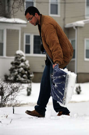 Jordan Holst shovels snow from his sidewalk on Homestead Avenue in Danbury, Conn., Tuesday, March 19, 2013, after an overnight snowfall. Photo: Carol Kaliff / The News-Times