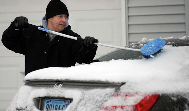 Jorge Correa clears the ice and snow from his car on Concord Road in Danbury, Conn. Tuesday morning, March 19, 2013, after an overnight snowfall. Photo: Carol Kaliff / The News-Times