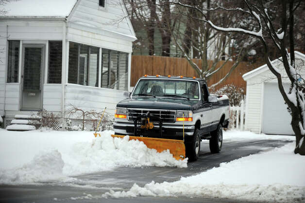 A plow driver clears a driveway of snow in Danbury, Conn. Tuesday, March 19, 2013, after an overnight snowfall. Photo: Carol Kaliff / The News-Times