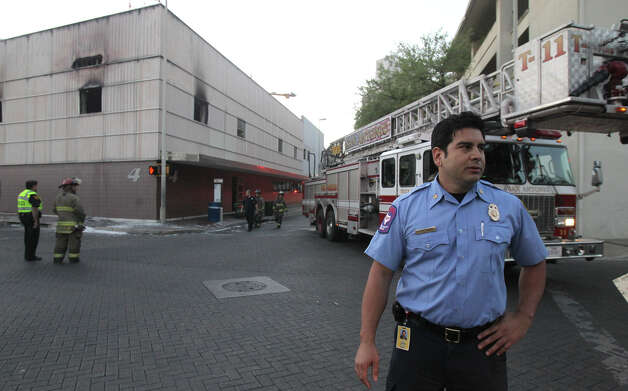 Oscar Gonzalez of the San Antonio Fire Department (right, foreground) speaks Tuesday March 19, 2013 about a fire that broke out about 5:00 a.m. at the WOAI television station at Navarro and St. Mary's. Gonzalez said the fire started on the building's second floor and took about an hour to contain. The cause of the fire is under investigation and there were no injuries during the incident. Photo: JOHN DAVENPORT, San Antonio Express-News / ©San Antonio Express-News/ Photo may be sold to the public