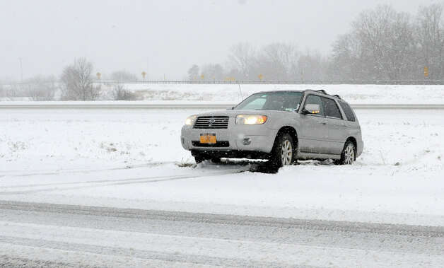 A Subaru is stuck in the median after sliding off I-87 northbound during a snow storm on Tuesday, March 19, 2013 in Colonie, N.Y. (Lori Van Buren / Times Union) Photo: Lori Van Buren