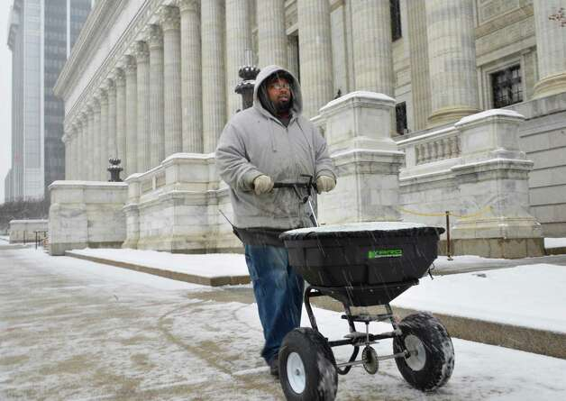 State Ed employee Jarvis Alexander spreads rock salt along the sidewalk in front of the State Education Building in Albany Tuesday March 19, 2013.  (John Carl D'Annibale / Times Union) Photo: John Carl D'Annibale / 00021622A