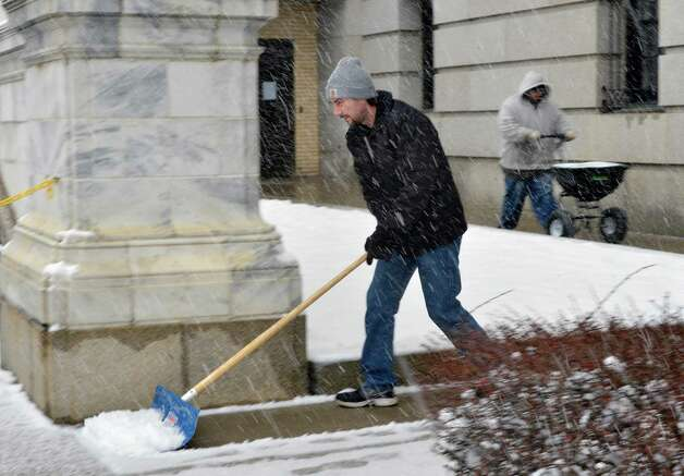 State Ed employees Bob Knight, left, and  Jarvis Alexander shovel and spread rock salt along the sidewalks around the State Education Building in Albany Tuesday March 19, 2013.  (John Carl D'Annibale / Times Union) Photo: John Carl D'Annibale / 00021622A