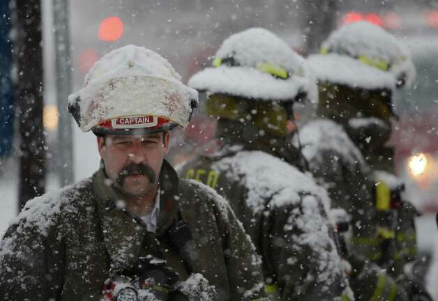 Schenectady Fire Department Captain Tim Tietz and his men are covered with snow March 19, 2013 while waiting to clear an accident with a fuel spill on Erie Boulevard in Schenectady, N.Y.(Skip Dickstein/Times Union) Photo: SKIP DICKSTEIN