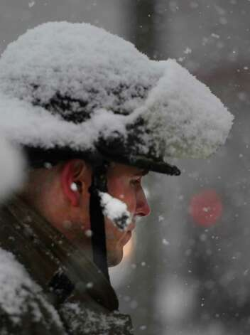 Schenectady Firefighter Sean Burns is covered with snow March 19, 2013 while waiting to clear an accident with a fuel spill on Erie Boulevard in Schenectady, N.Y.(Skip Dickstein/Times Union) Photo: SKIP DICKSTEIN