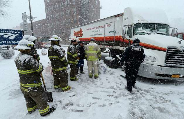 Schenectady Firefighters and Police officers are covered while March 19, 2013 while waiting to clear an accident with a fuel spill on Erie Boulevard in Schenectady, N.Y.(Skip Dickstein/Times Union) Photo: SKIP DICKSTEIN