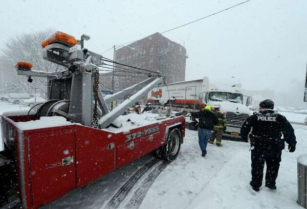 A tow vehicle hooks up to a damaged tractor trailer March 19, 2013 at the scene of an accident with a fuel spill on Erie Boulevard in Schenectady, N.Y.(Skip Dickstein/Times Union) Photo: SKIP DICKSTEIN