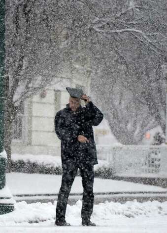 A man uses a notebook to shield himself from the heavy snow on Franklin Street March 19, 2013,  in Schenectady, N.Y.(Skip Dickstein/Times Union) Photo: SKIP DICKSTEIN