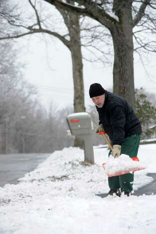 Shaun Supp shovels his driveway on Kimberly Lane in Ansonia, Conn. on Tuesday March 19, 2013. An overnight snow fall dropped about 3 to 4 inches in the valley area. Photo: Cathy Zuraw / Connecticut Post