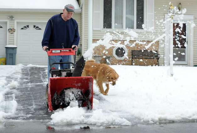 "Paul Heon and ""Yellow Dog"" clear a driveway on White Oak Rd. in Ansonia, Conn. on Tuesday March 19, 2013. Overnight snowfall dropped about 3-4 inches in the valley area. Photo: Cathy Zuraw / Connecticut Post"